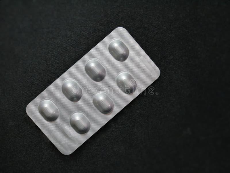 Bloco de bolha de prata de comprimidos da medicamentação no fundo preto com foco seletivo foto de stock royalty free