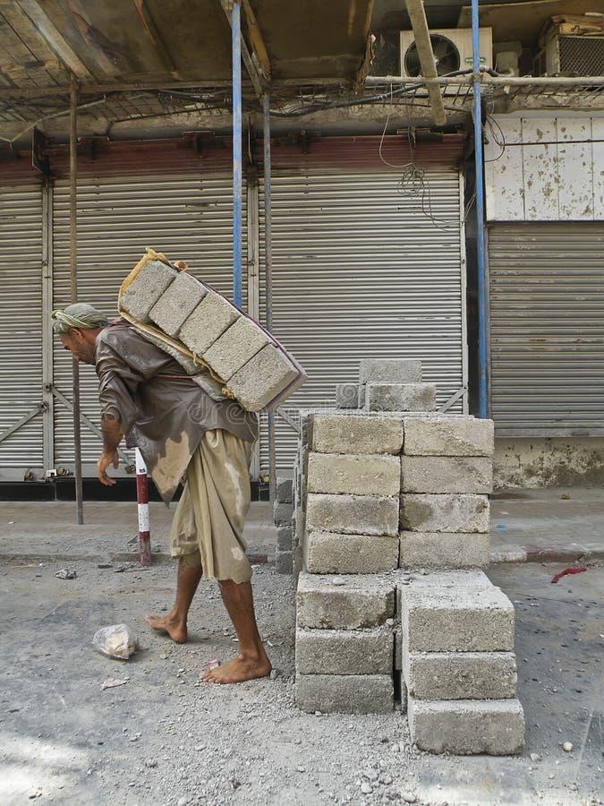 Bloco de cimento levando do trabalhador da construção imagem de stock