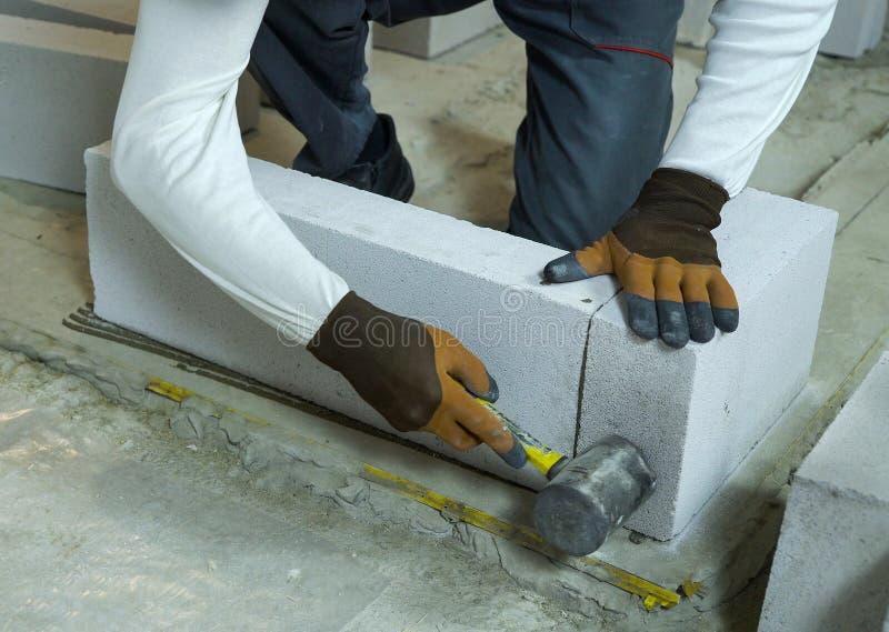 Bloco de cimento ventilado batida do trabalhador da construção com martelo de borracha fotografia de stock royalty free