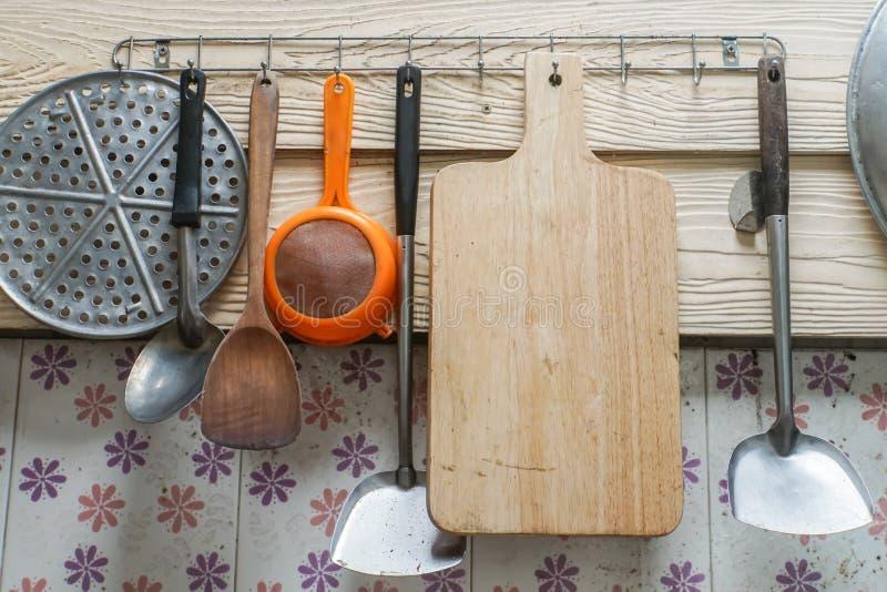 Bloco de desbastamento de madeira com cair do kitchenware na parede da cozinha imagem de stock royalty free