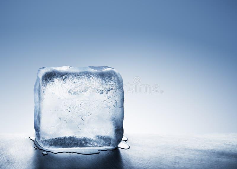 Bloco de gelo azul frio que derrete na poça da água fotografia de stock