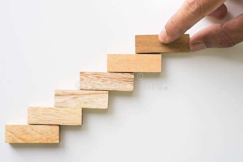 Bloco de madeira aranging da mão que empilha como a escada da etapa fotografia de stock royalty free