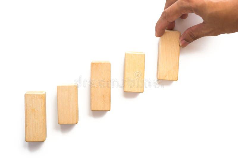 Bloco de madeira aranging da mão que empilha como a escada da etapa imagem de stock royalty free