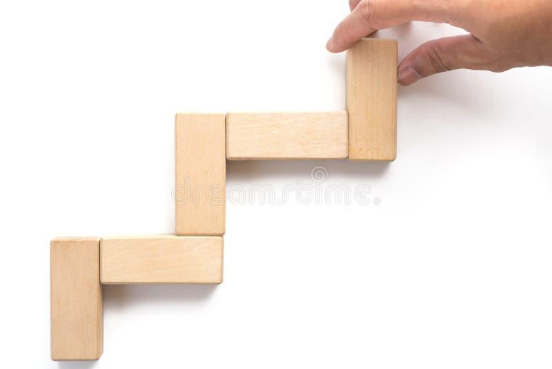 Bloco de madeira aranging da mão que empilha como a escada da etapa fotos de stock