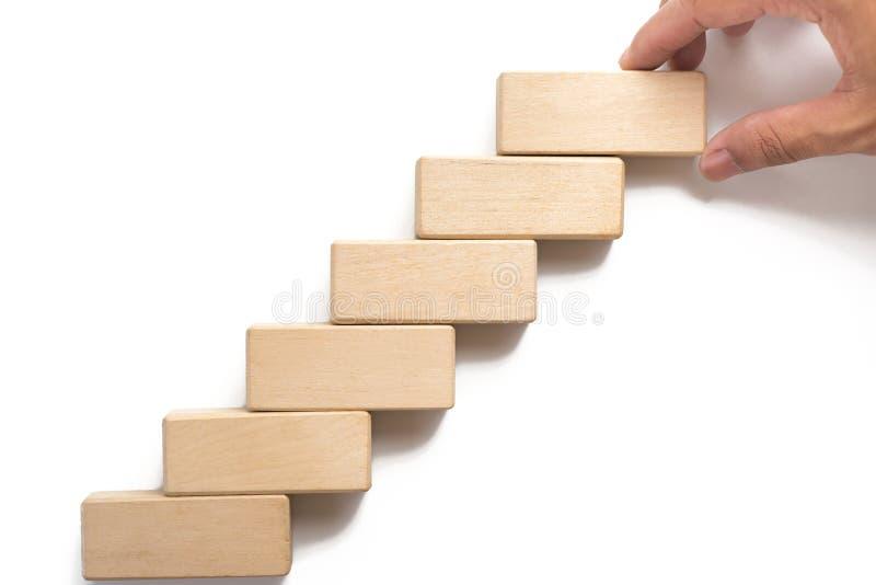 Bloco de madeira aranging da mão que empilha como a escada da etapa imagens de stock
