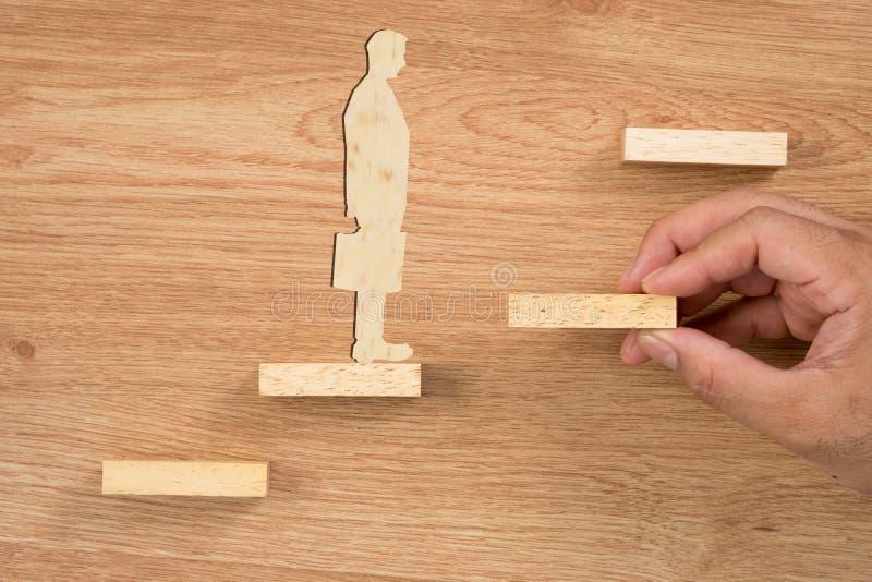 Bloco de madeira aranging da mão que empilha como a escada da etapa Concep do negócio fotos de stock