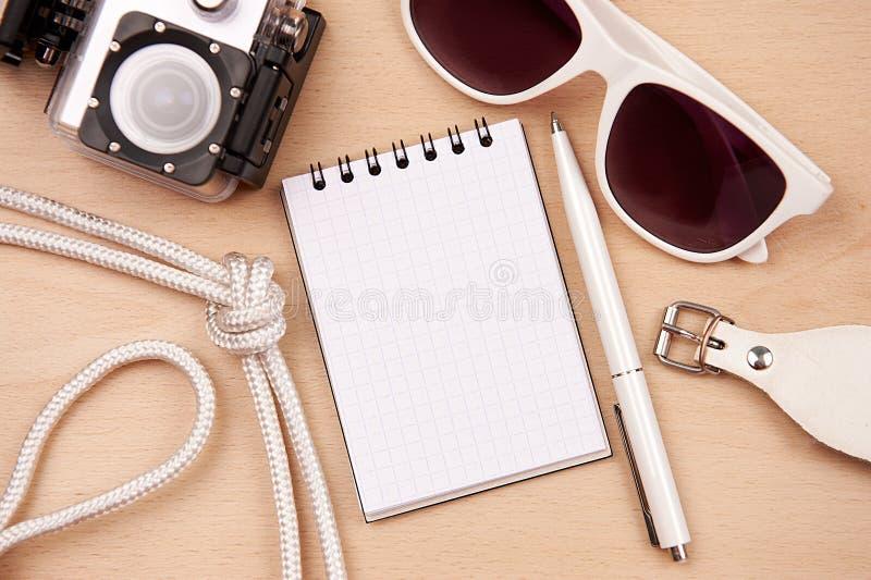Bloco de notas, óculos de sol e pena na tabela foto de stock royalty free