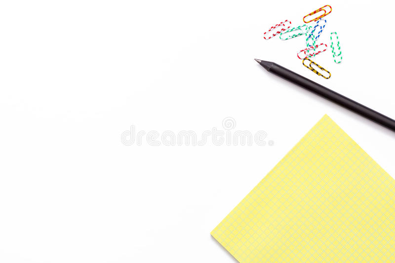 Bloco de notas amarelo, pena preta e clipe de papel colorido no fundo branco Conceito de trabalho mínimo para o escritório, escol fotografia de stock