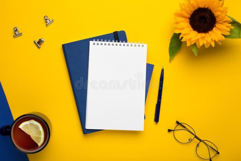 Bloco de notas branco com caderno azul e pena no fundo amarelo fotos de stock