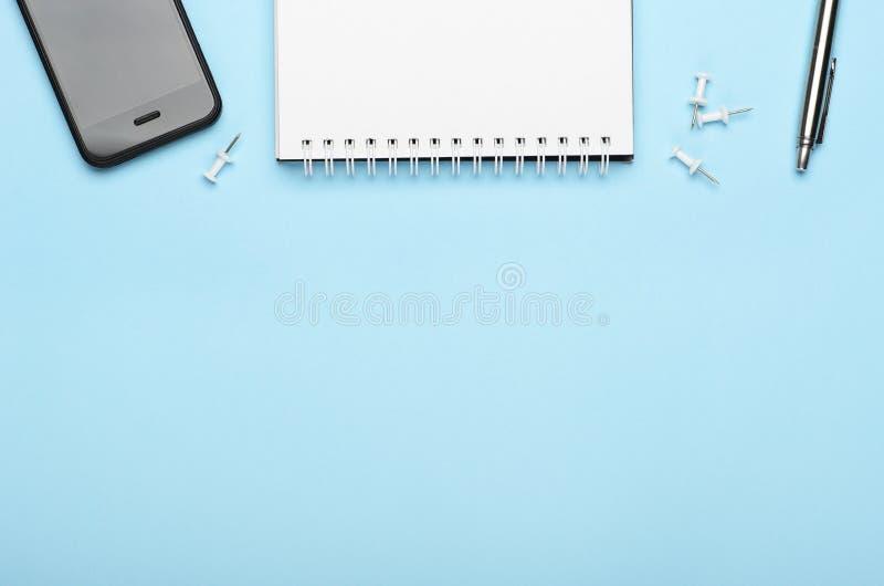 Bloco de notas branco com pena, botões e telefone do metal em um fundo azul Tabela do escritório, composição mínima, espaço da có imagens de stock royalty free