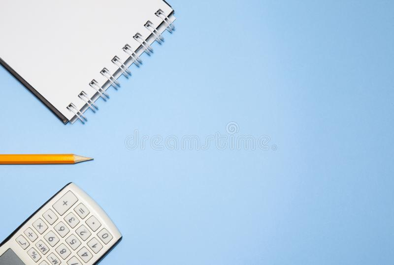 Bloco de notas, calculadora e lápis no fundo azul imagem de stock royalty free