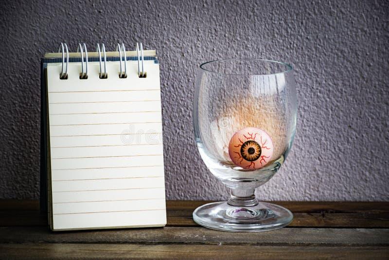 Bloco de notas com a bola do olho no vidro no fundo da madeira e da parede Usando o papel de parede ou o fundo para a imagem do d imagens de stock royalty free