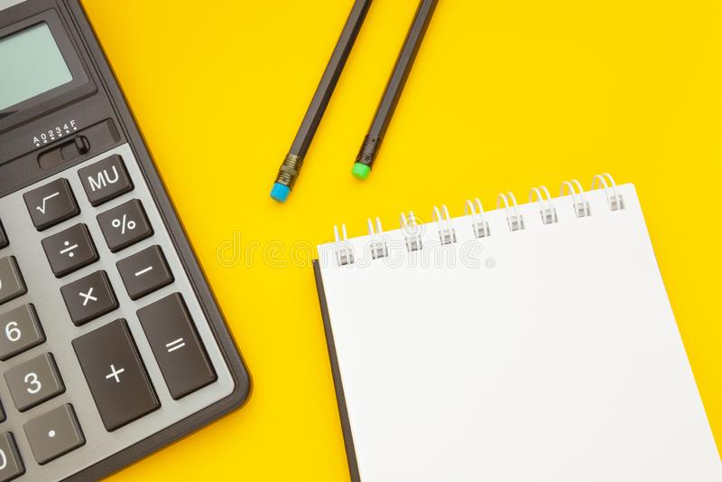 Bloco de notas com dois lápis e uma calculadora em um fundo amarelo fotografia de stock royalty free