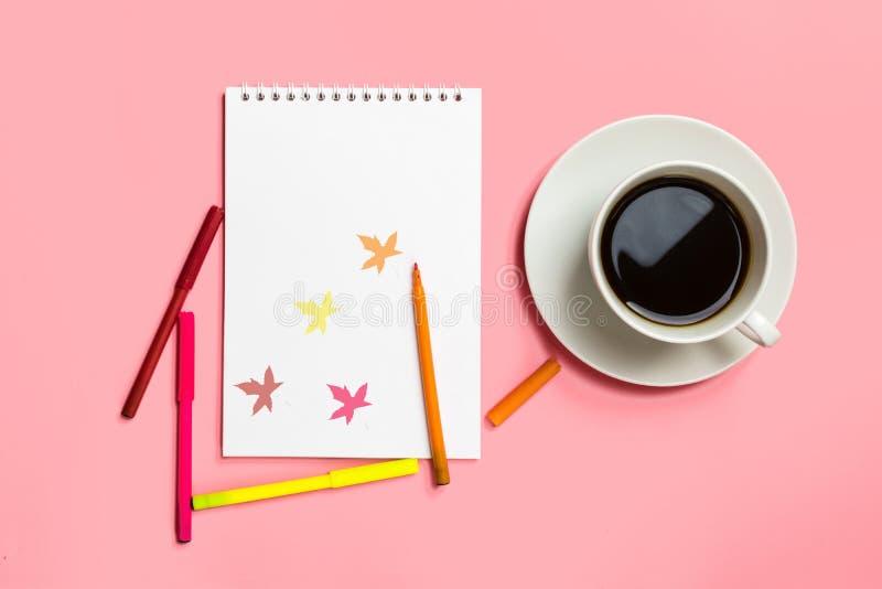 Bloco de notas com folhas, canetas com ponta de feltro coloridas, copo com café no fundo do rosa pastel Outono do conceito Lugar  fotos de stock royalty free