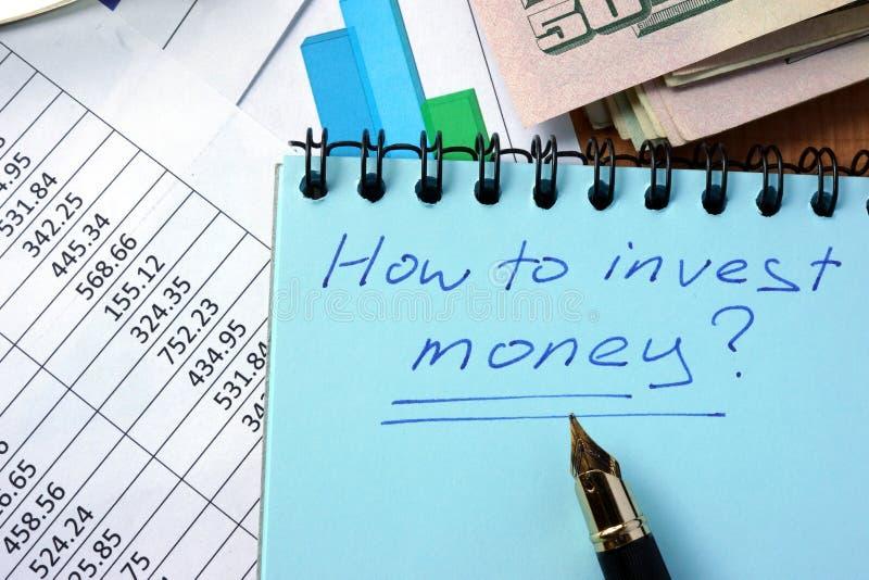 Bloco de notas com inscrição como investir o dinheiro fotos de stock