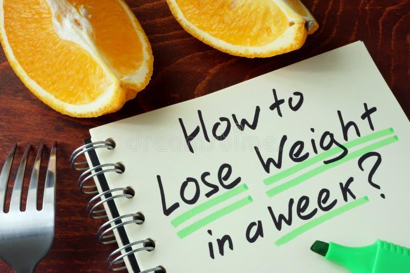 Bloco de notas com sinal como perder o peso em uma semana fotos de stock