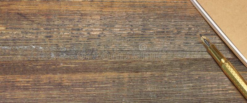 Bloco de notas com a tabela de Pen On The Old Wood da fonte do ouro imagem de stock