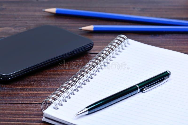 Bloco de notas com telefone e lápis da pena na mesa imagens de stock