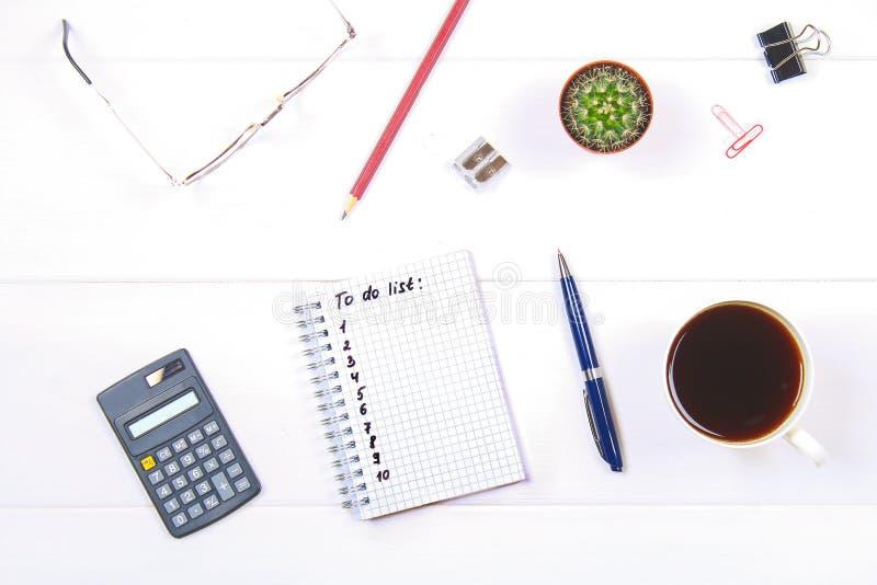 Bloco de notas com texto: Para fazer a tabela branca da lista com calculadora, cacto, papel de nota, caneca de café, pena, vidros imagens de stock