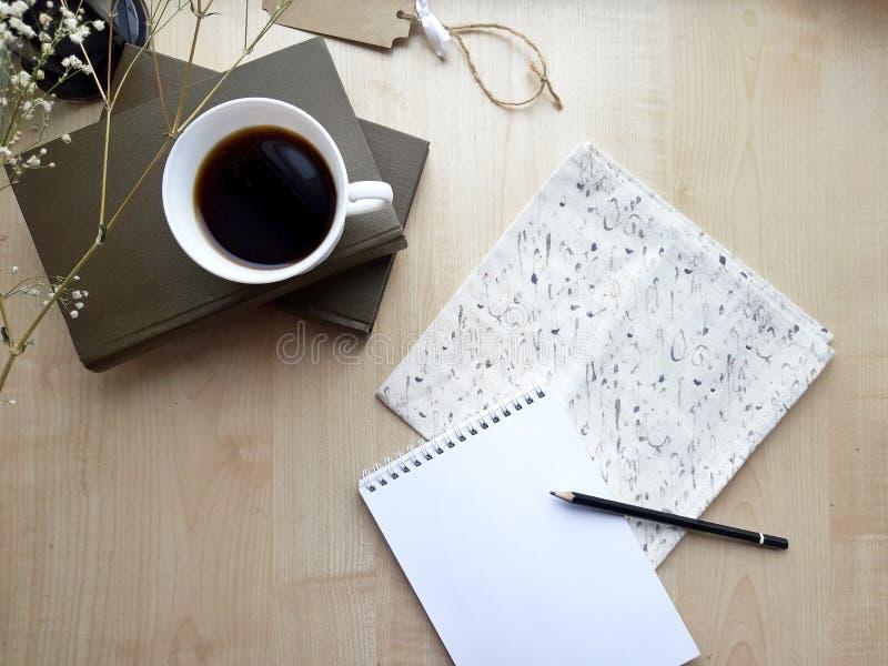 Bloco de notas, copo de café e livros vazios na tabela de madeira imagem de stock royalty free