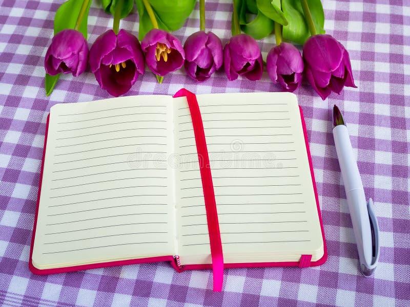 Bloco de notas cor-de-rosa com papel alinhado, a pena de esferográfica branca e uma fileira de tulipas roxas em um fundo quadricu imagens de stock