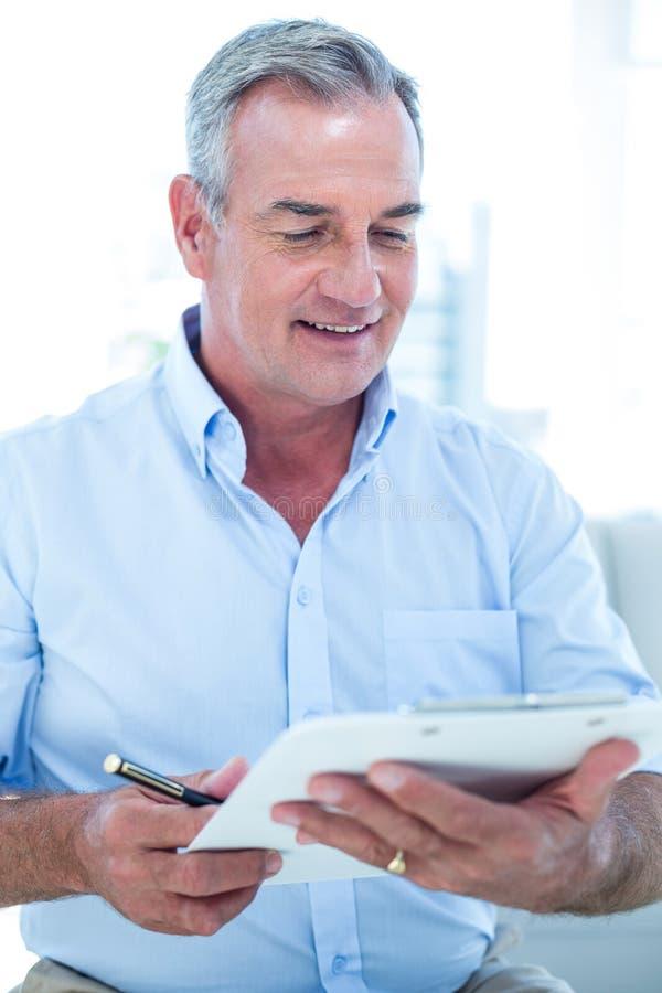 Bloco de notas da leitura do homem de negócios ao sentar-se foto de stock royalty free