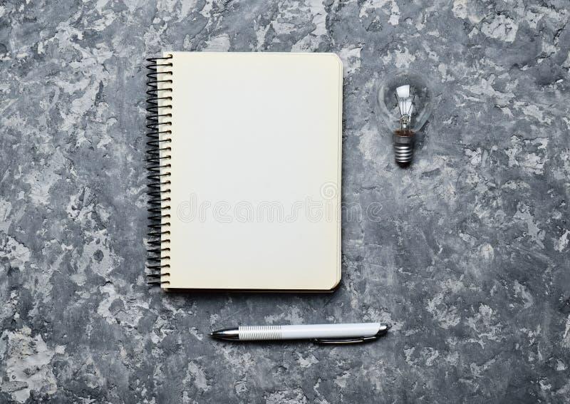 Bloco de notas do moderno, pena e bulbo incandescente em uma tabela concreta Eu tenho uma ideia! Inspiração para o escritor Vista imagens de stock royalty free