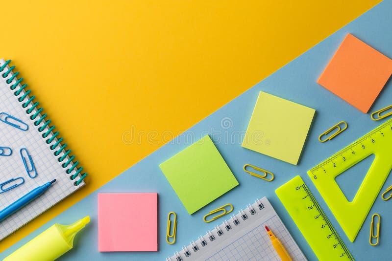 Bloco de notas e artigos de papelaria coloridos da escola no fundo colorido fotografia de stock