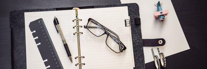 Bloco de notas e artigos de papelaria em um fundo preto Planejador para o neg?cio e o estudo Fãs da BANDEIRA dos artigos de papel fotografia de stock royalty free
