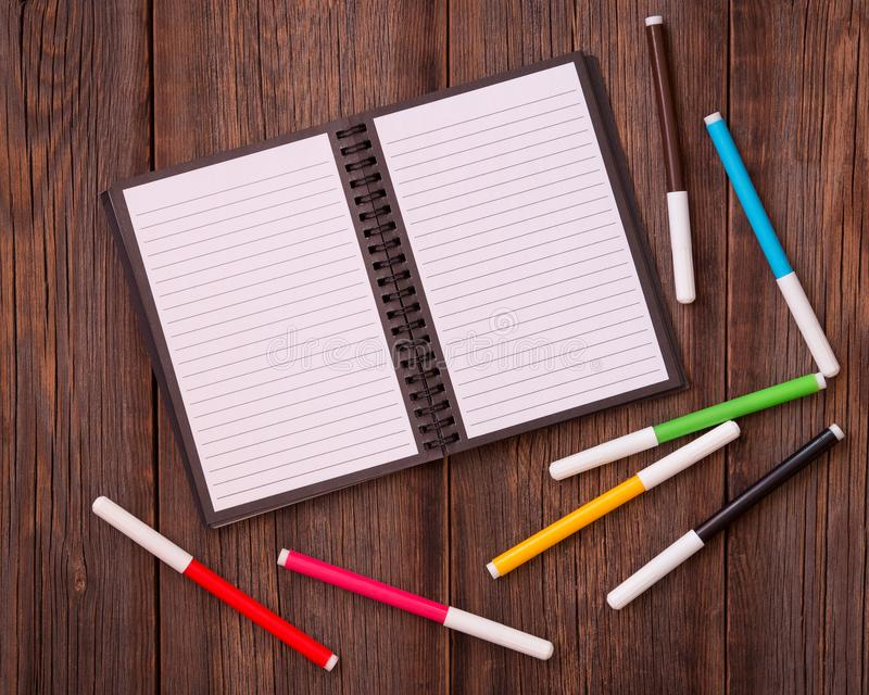 Bloco de notas e canetas com ponta de feltro coloridas em um fundo de madeira imagens de stock