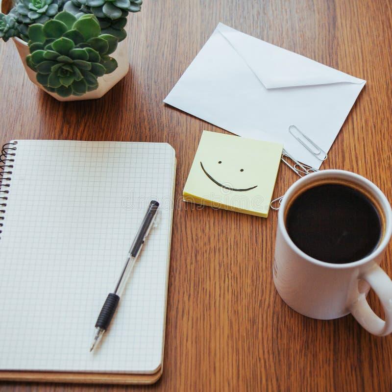 bloco de notas e pena ao lado de uma xícara de café em uma tabela de madeira fora em um café imagem de stock royalty free