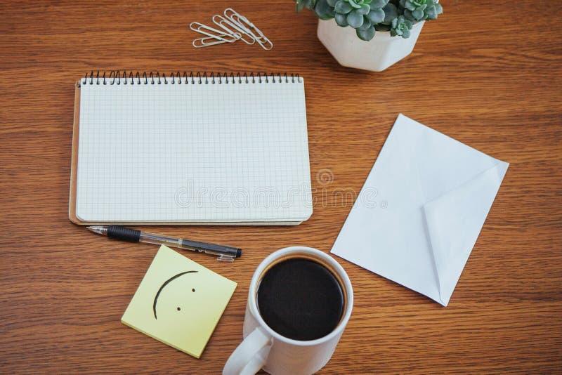 bloco de notas e pena ao lado de uma xícara de café em uma tabela de madeira fora em um café imagem de stock
