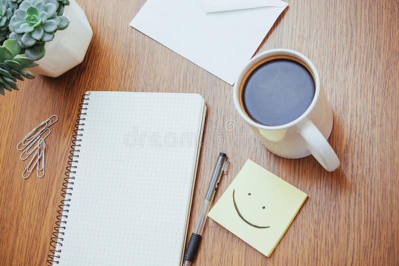 bloco de notas e pena ao lado de uma xícara de café em uma tabela de madeira fora em um café foto de stock royalty free