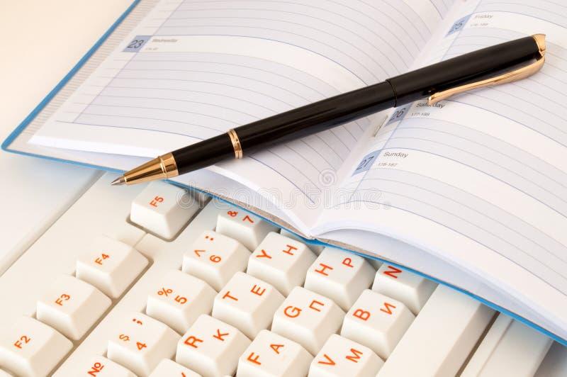 Bloco de notas e pena no teclado imagens de stock royalty free