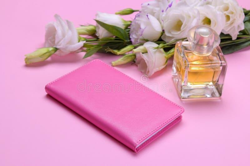 bloco de notas e perfume fêmeas ao lado das flores do eustoma em um fundo cor-de-rosa brilhante fotografia de stock