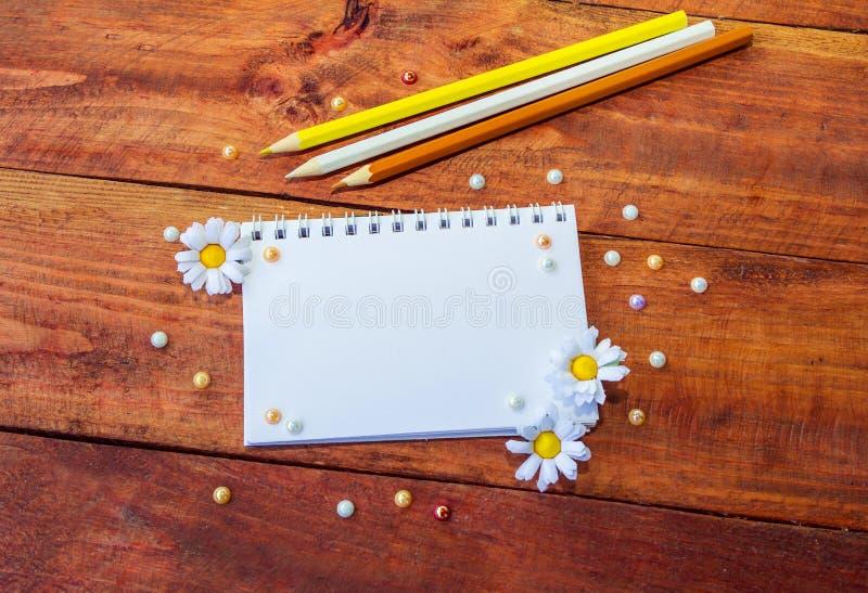 Bloco de notas, flores e lápis fotografia de stock