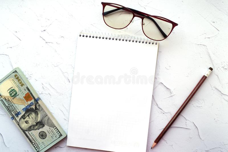 Bloco de notas, lápis, vidros e dólares americanos em um fundo claro fotos de stock royalty free