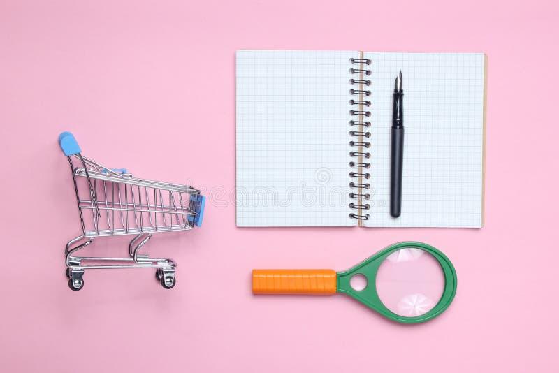 Bloco de notas, lente de aumento, trole de compra no fundo cor-de-rosa do patel imagens de stock royalty free