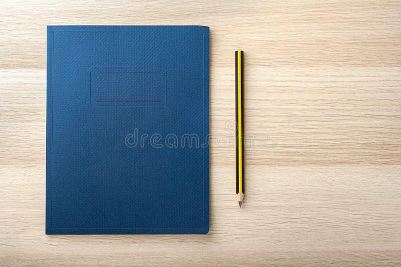 Bloco de notas na mesa de madeira com lápis fotografia de stock