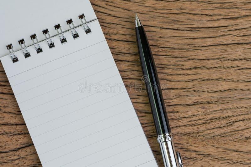 Bloco de notas de papel pequeno com página vazia, pena na tabela de madeira usando-se como a nota da reunião, redigindo a mensage imagens de stock