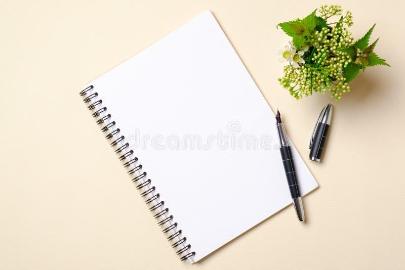 Bloco de notas de papel vazio com bandeja e planta das flores no fundo bege Vista superior, composi??o lisa da configura??o Conce imagem de stock