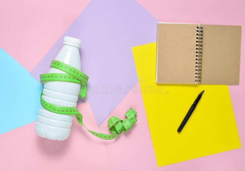 Bloco de notas para o plano de compilação da dieta, garrafa do kefir envolvida com a régua no fundo de papel colorido foto de stock