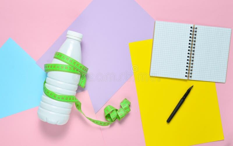 Bloco de notas para o plano de compilação da dieta, garrafa do kefir envolvida com a régua no fundo de papel colorido Vista super fotografia de stock