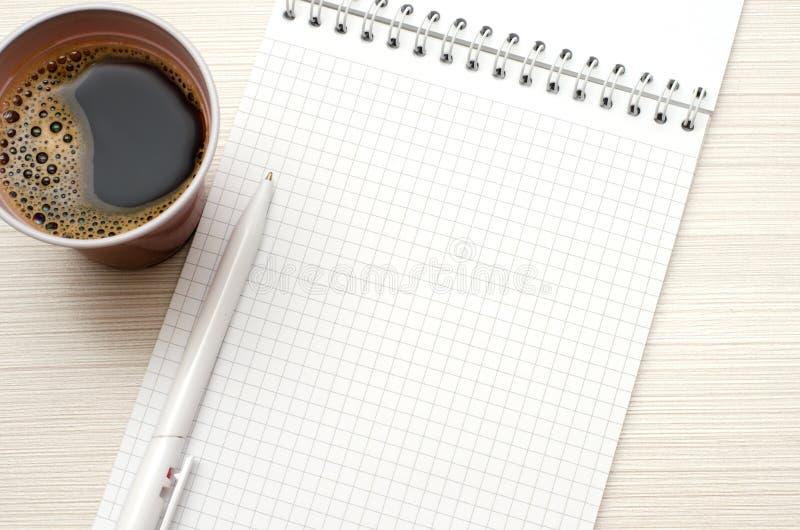 Bloco de notas para o texto Pena branca, xícara de café imagem de stock royalty free