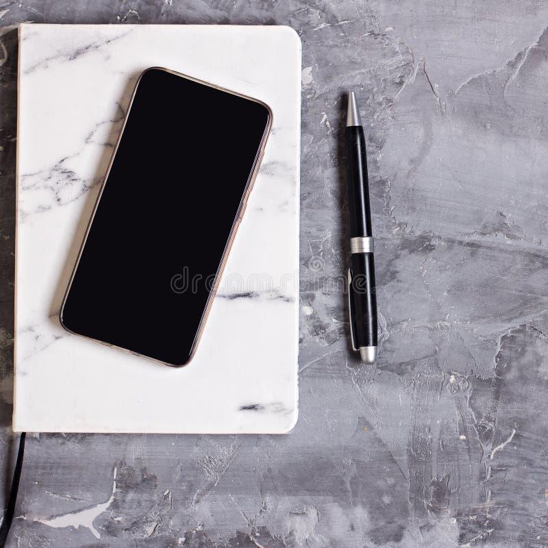 Bloco de notas, telefone celular, pena, planta carnuda, vidros, xícara de café em um fundo cinzento do cimento fotografia de stock royalty free