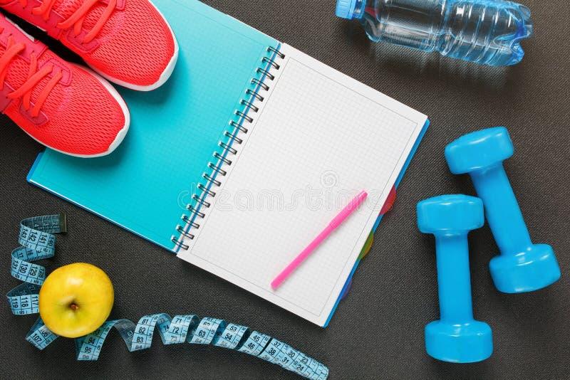 Bloco de notas, uma garrafa da água, uma maçã, uma corda de salto, pesos Dieta saudável, estilo de vida, conceito dos pesos imagem de stock royalty free