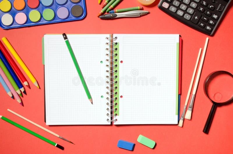 Bloco de notas vazio com artigos de papelaria da escola e do escritório, fundo vermelho foto de stock royalty free