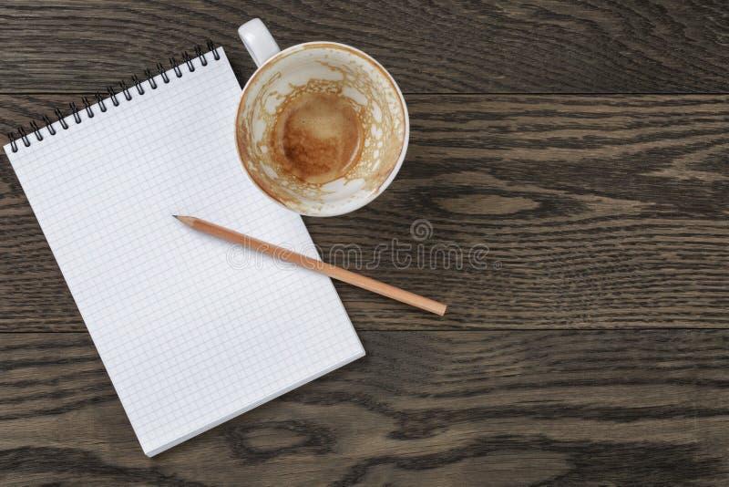 Bloco de notas vazio com lápis e o copo de café vazio na tabela de madeira imagem de stock