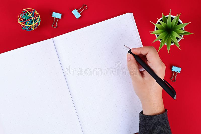 Bloco de notas vazio na tabela vermelha, planta, pena Vista superior, configura??o lisa Modelo, espa?o da c?pia imagem de stock royalty free