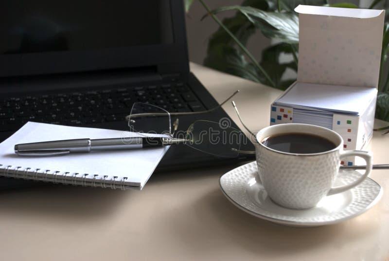 Bloco de notas vazio sobre o copo do portátil e de café imagens de stock royalty free